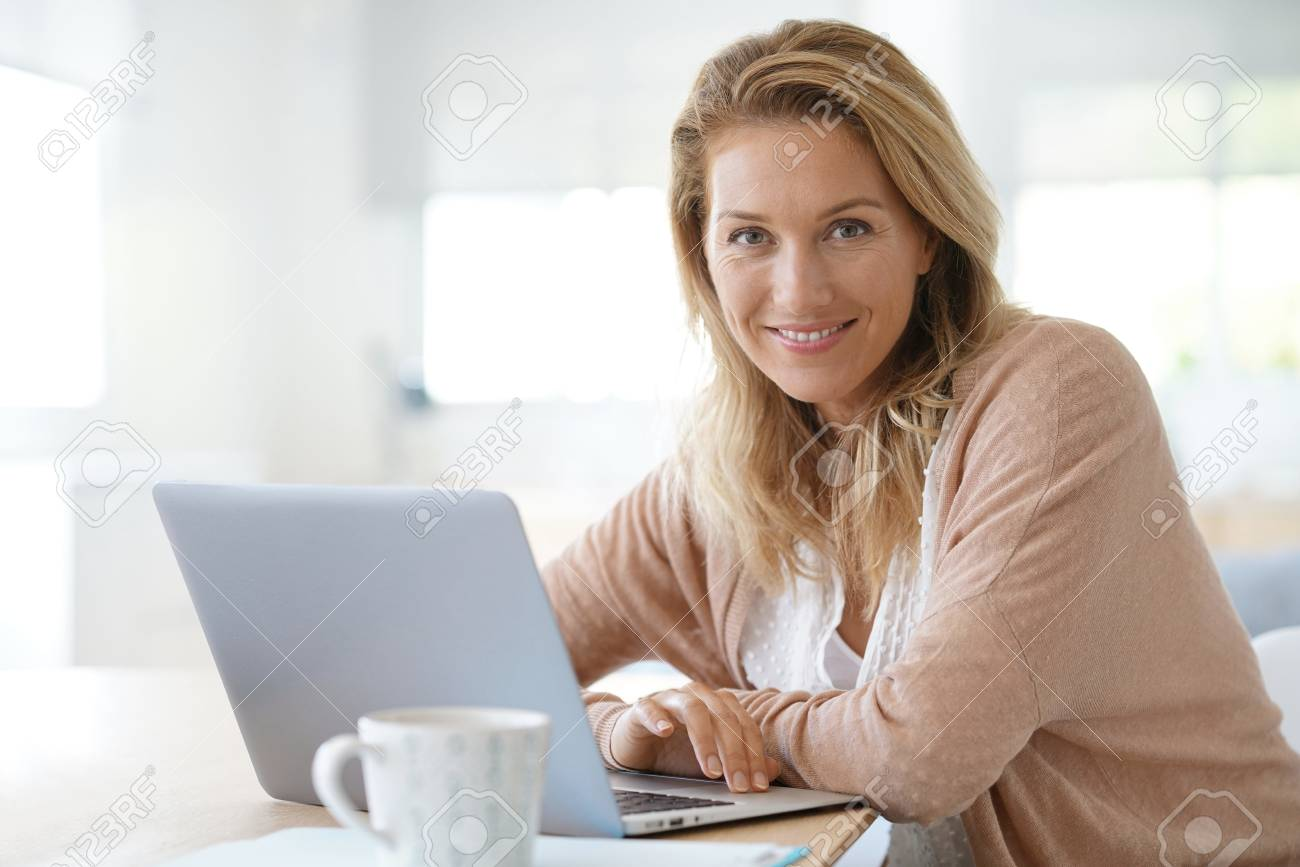 Attractive blond woman working on laptop computer at home - 86417220