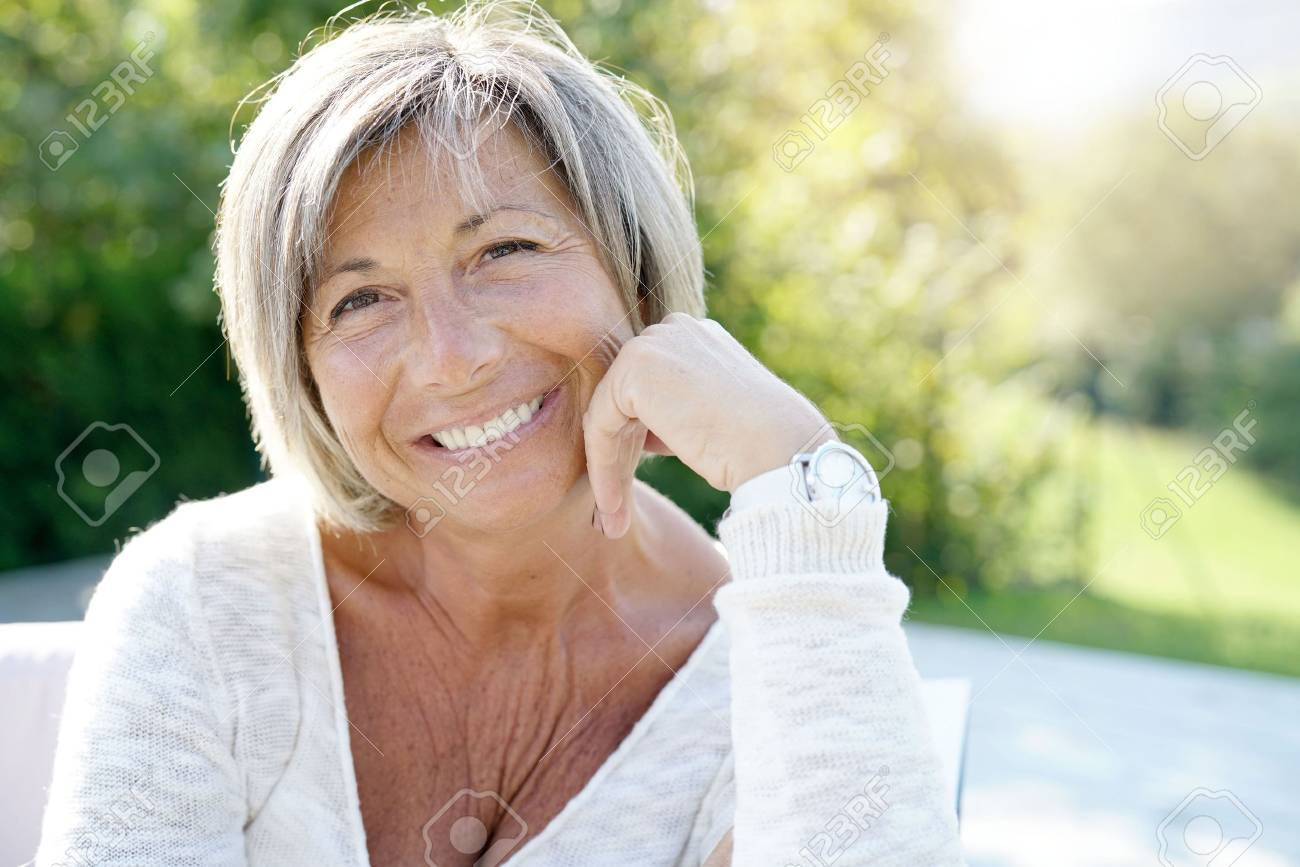 Portrait of cheerful senior woman relaxing in outdoors sofa - 87651502