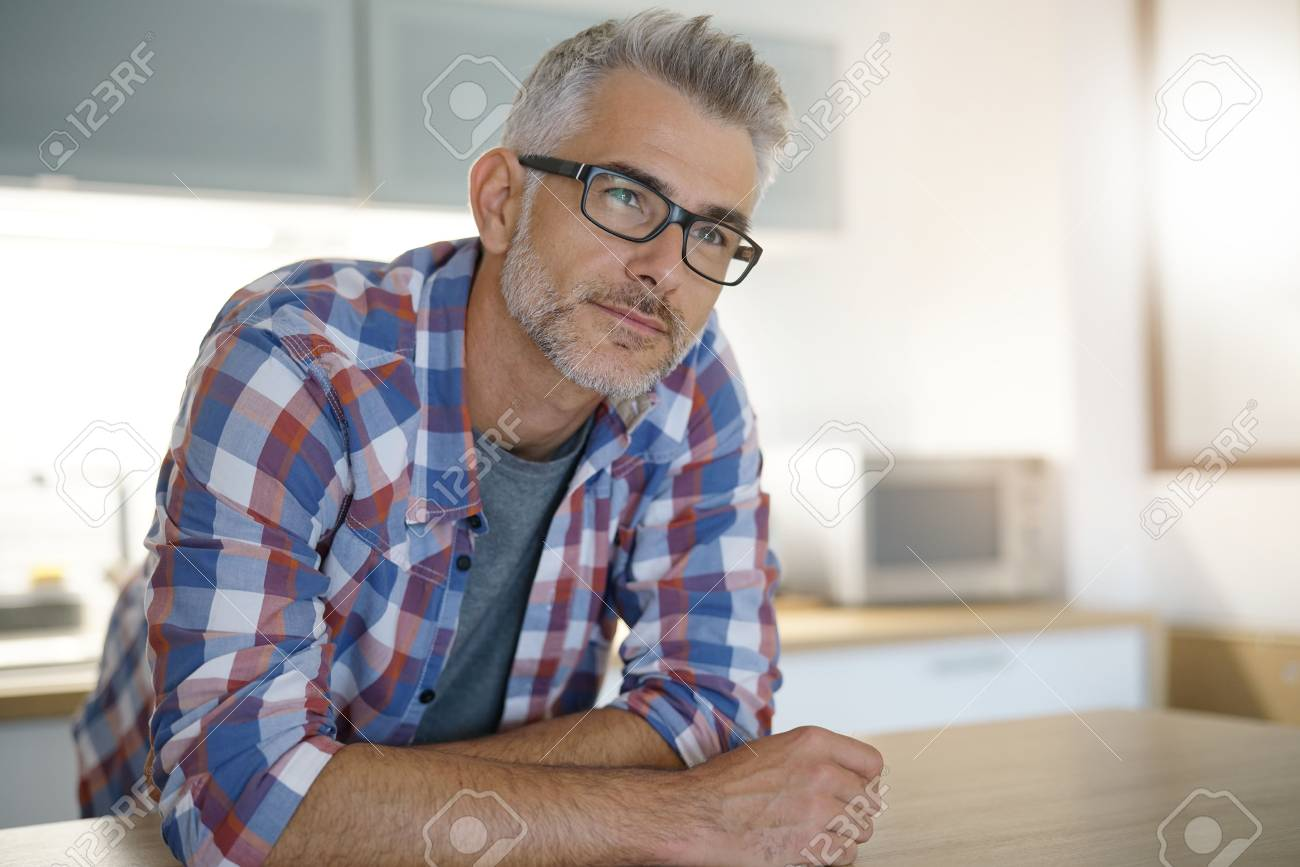 Middle-aged man with grey hair in home kitchen - 89006226