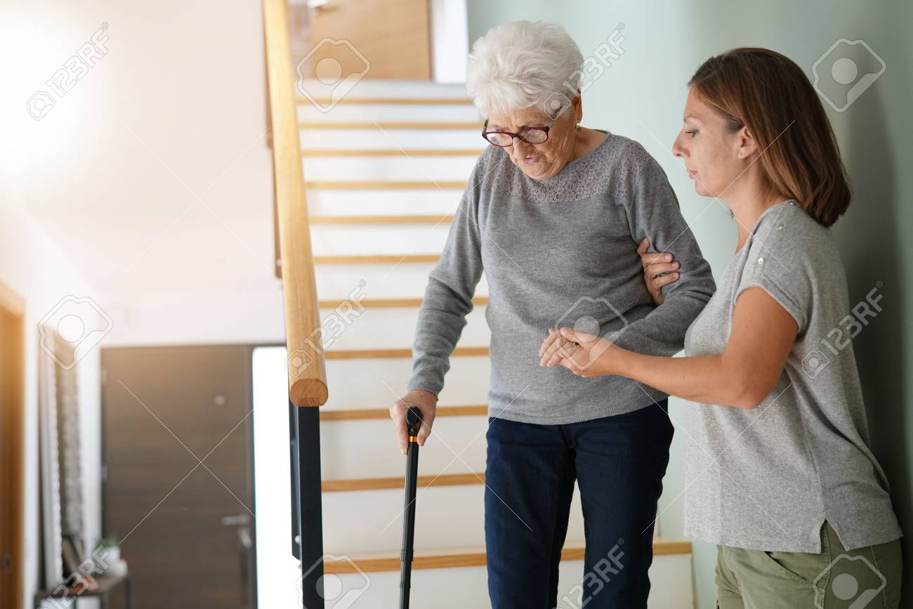 Homecare helping elderly woman going down the stairs - 90536105