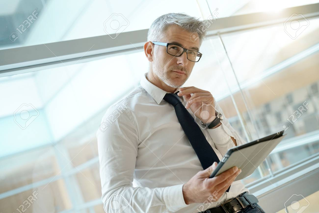 Businessman in office connected with digital tablet - 90549591
