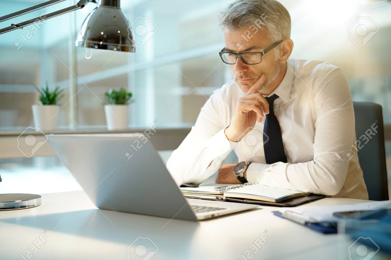 Businessman working on laptop in office, being concerned - 90549833