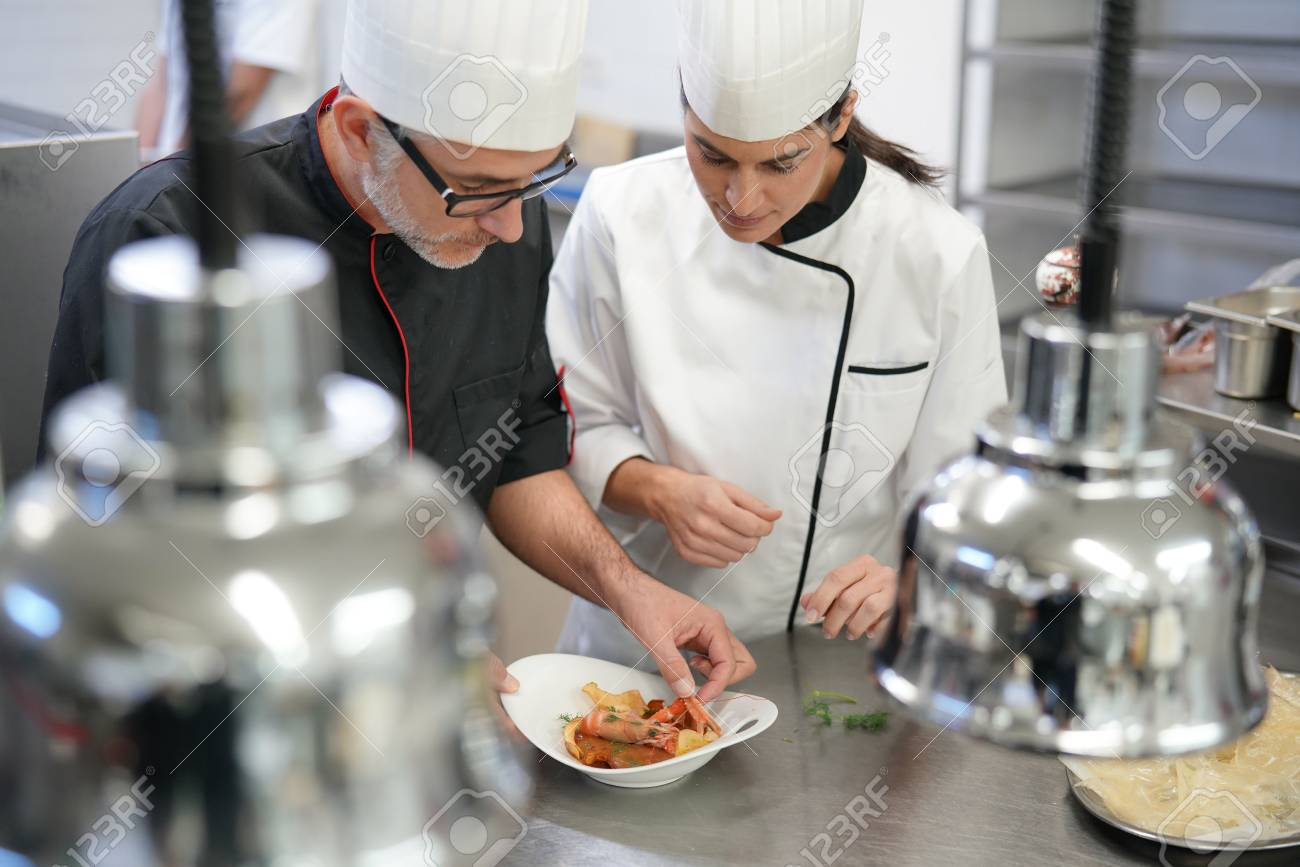 professional cook chefs in kitchen improving dish composition stock