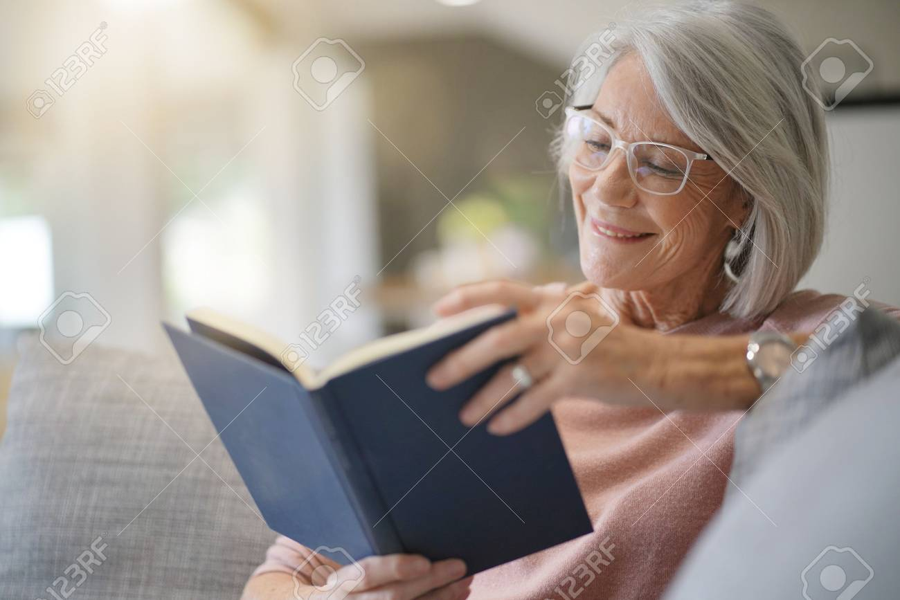 Senior woman reading on couch at home - 110688318