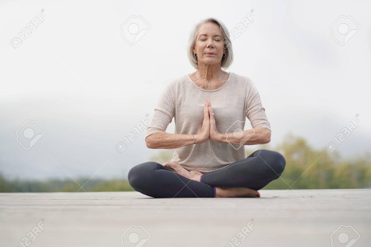 Serene senior woman meditating outdoors - 110688632