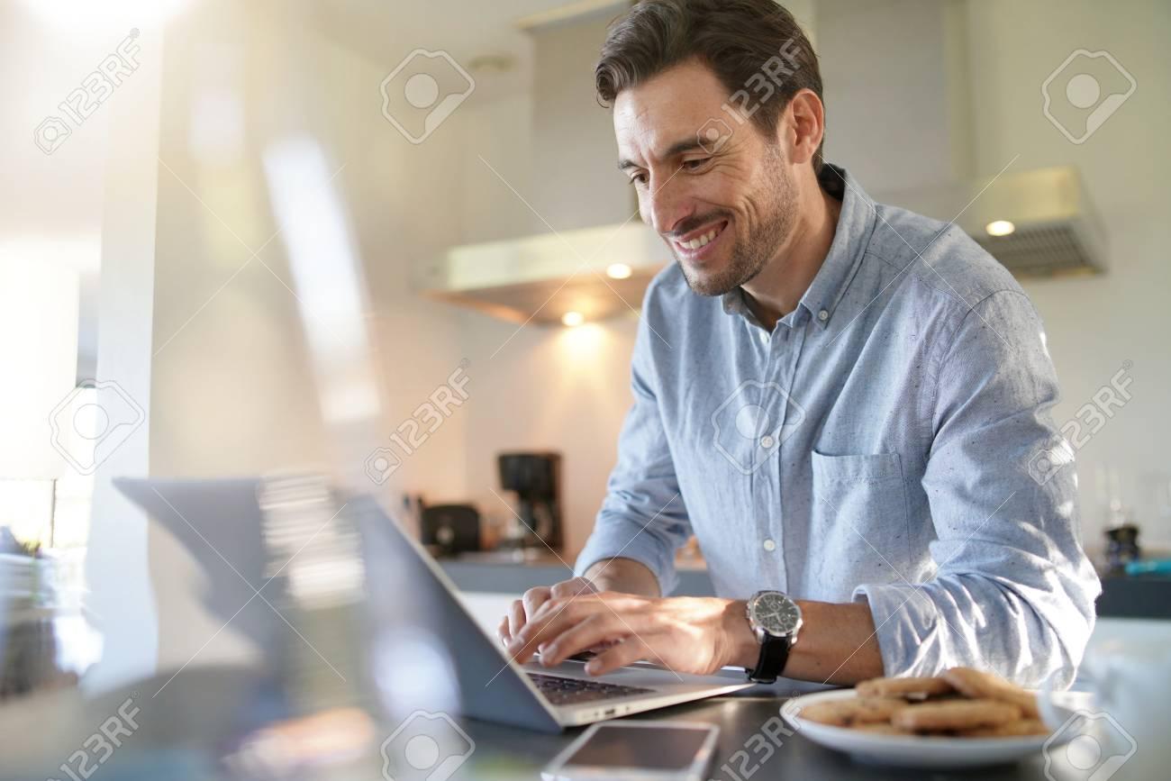 Handsome man with computer in modern kitchen - 112560607