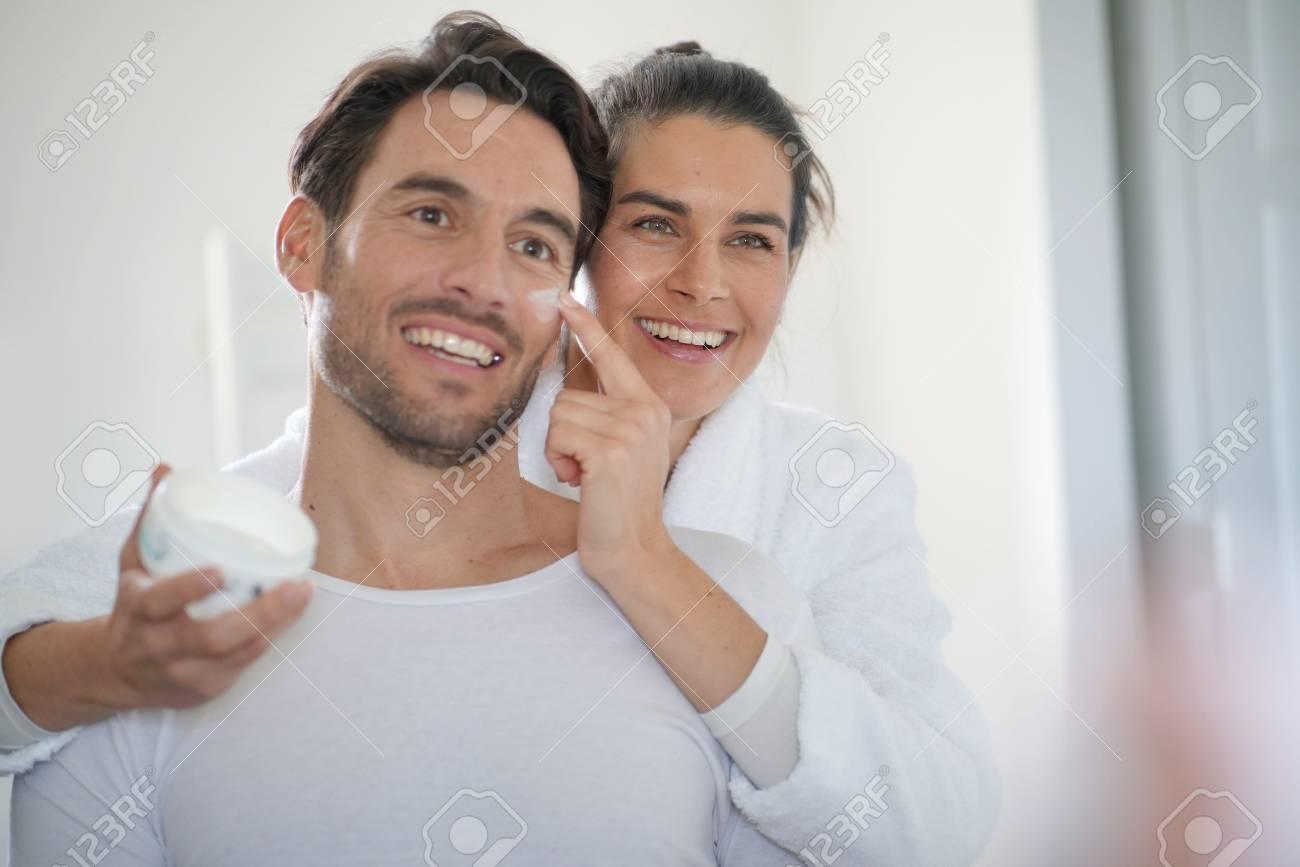 Stunning brunette applying face cream on her handsome partner - 112560661