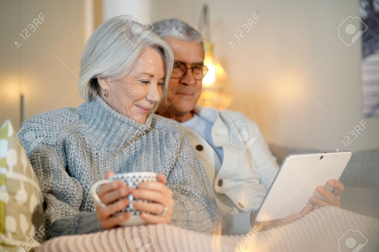 Senior couple relaxing at home on couch with tablet - 113925863