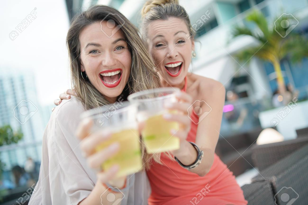 Two attractive funloving friends partying with drinks on rooftop bar in city - 116321326