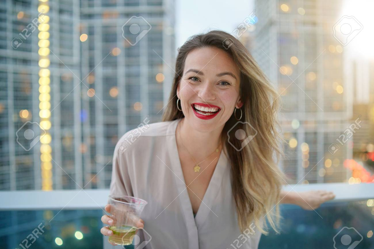 Atttractive elegant young woman smiling at camera on rooftop bar in city - 116321383