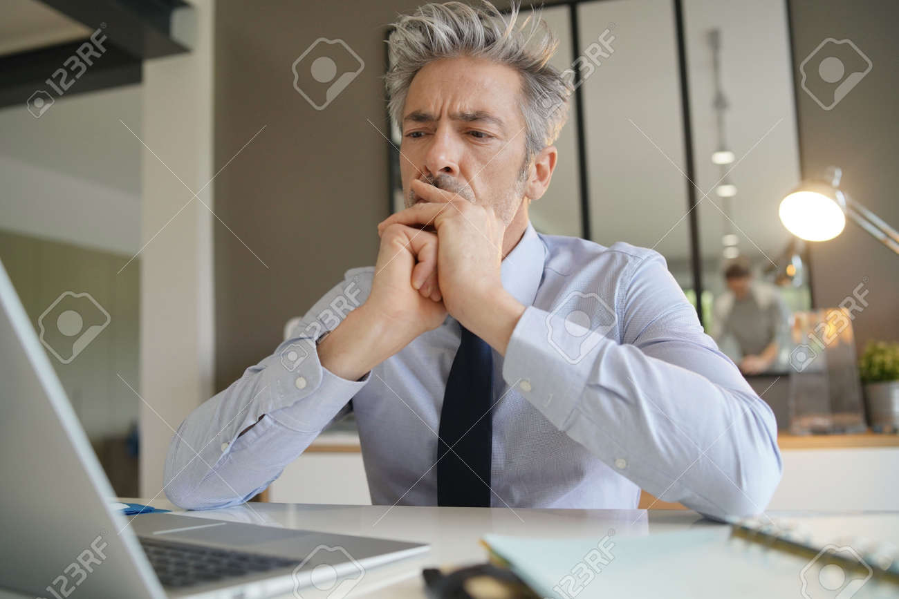 Handsome businessman in office contemplating - 120544552
