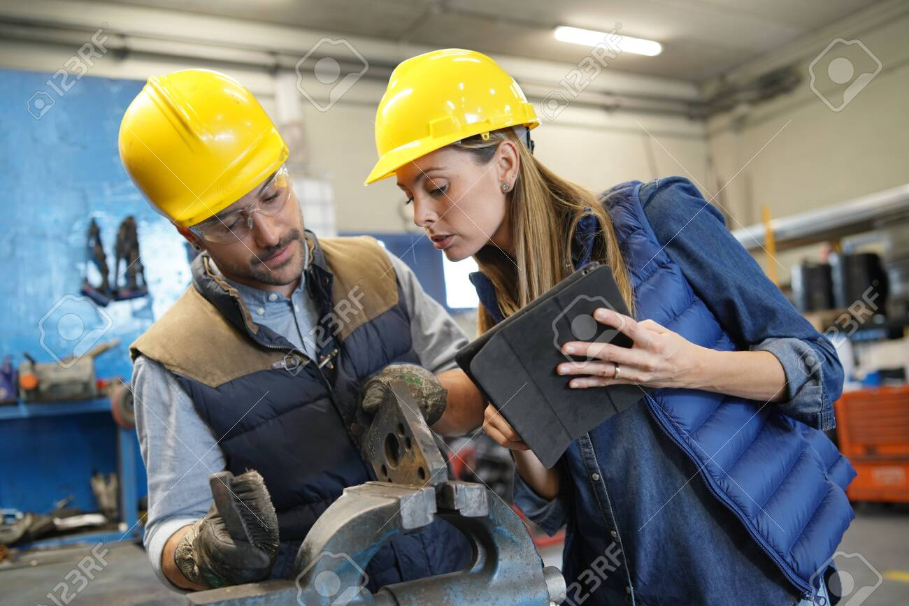 Mechanical workshop manager giving instructions to employee - 134959938