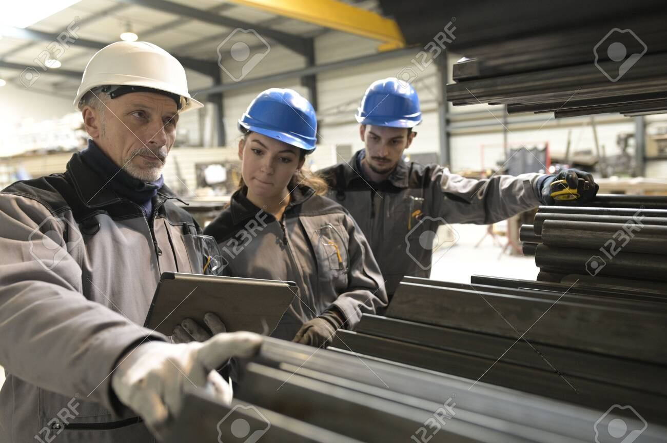 Steelwork instructor with young apprentice in workshop - 138606000