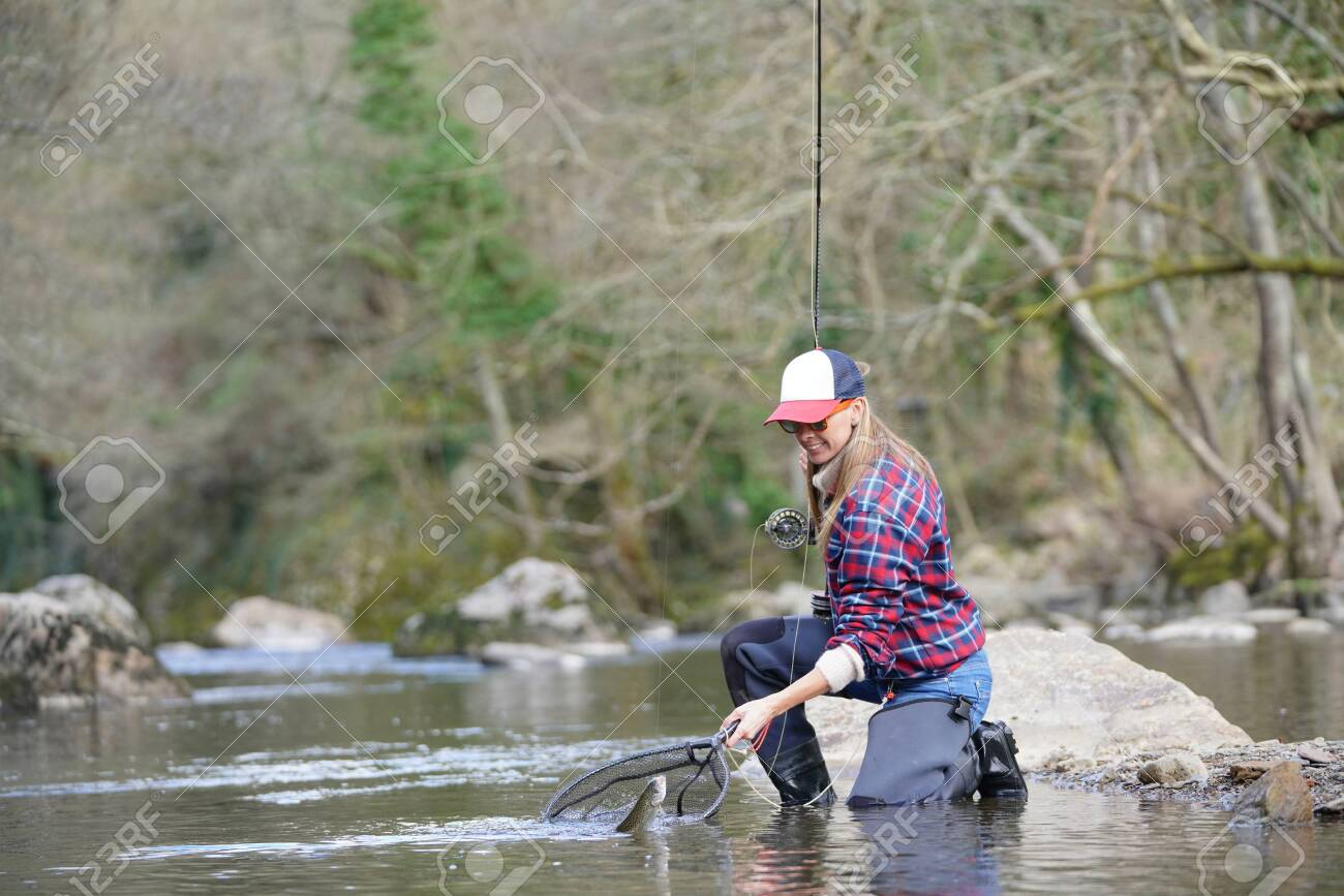 Woman catching rainbow trout fly in river - 144835179