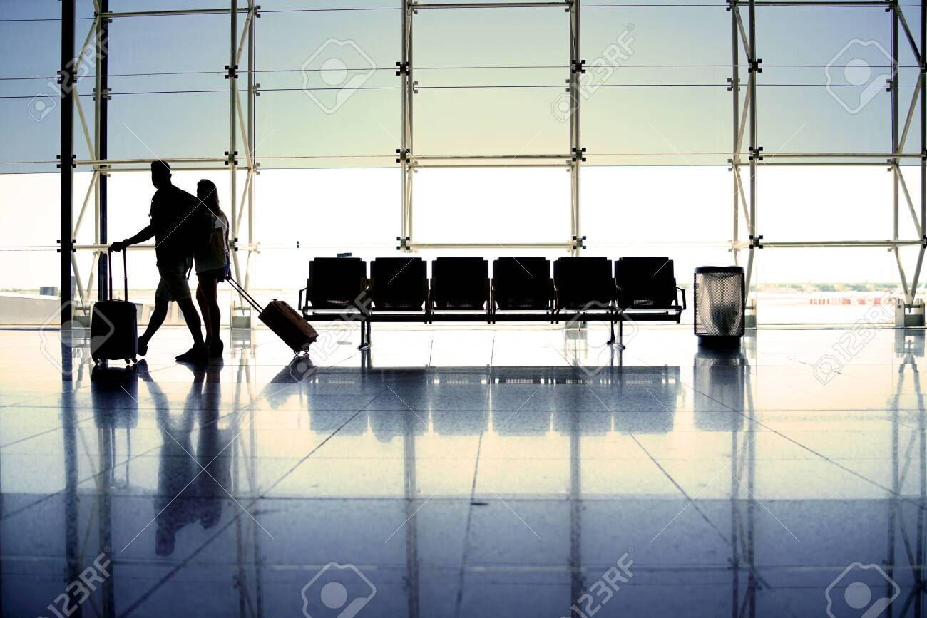 People pulling suitcases in airport hallway - 149053660