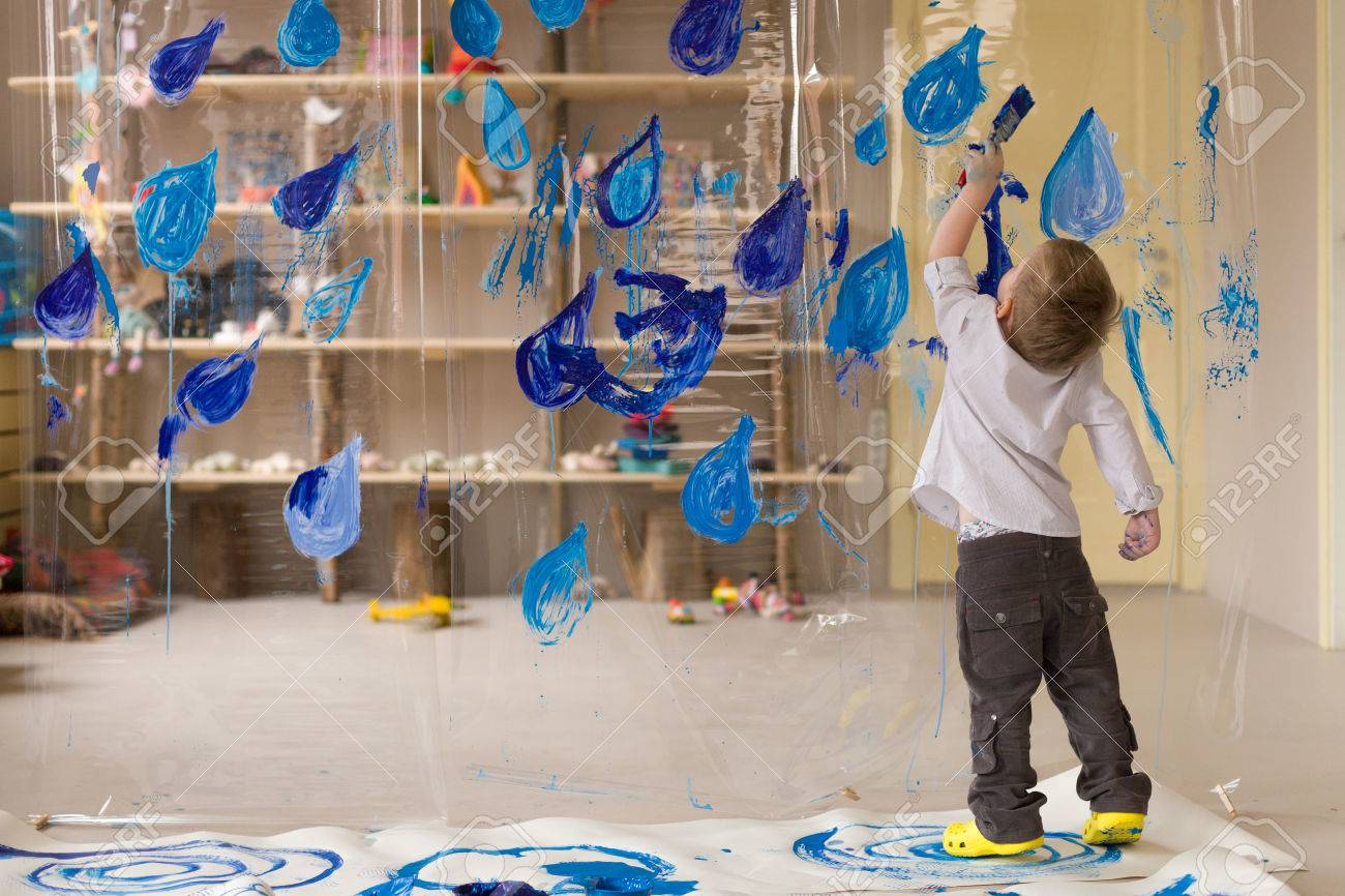 A 3 Years Old Boy In A White Shirt Is Drawing Blue Drops Of Rain