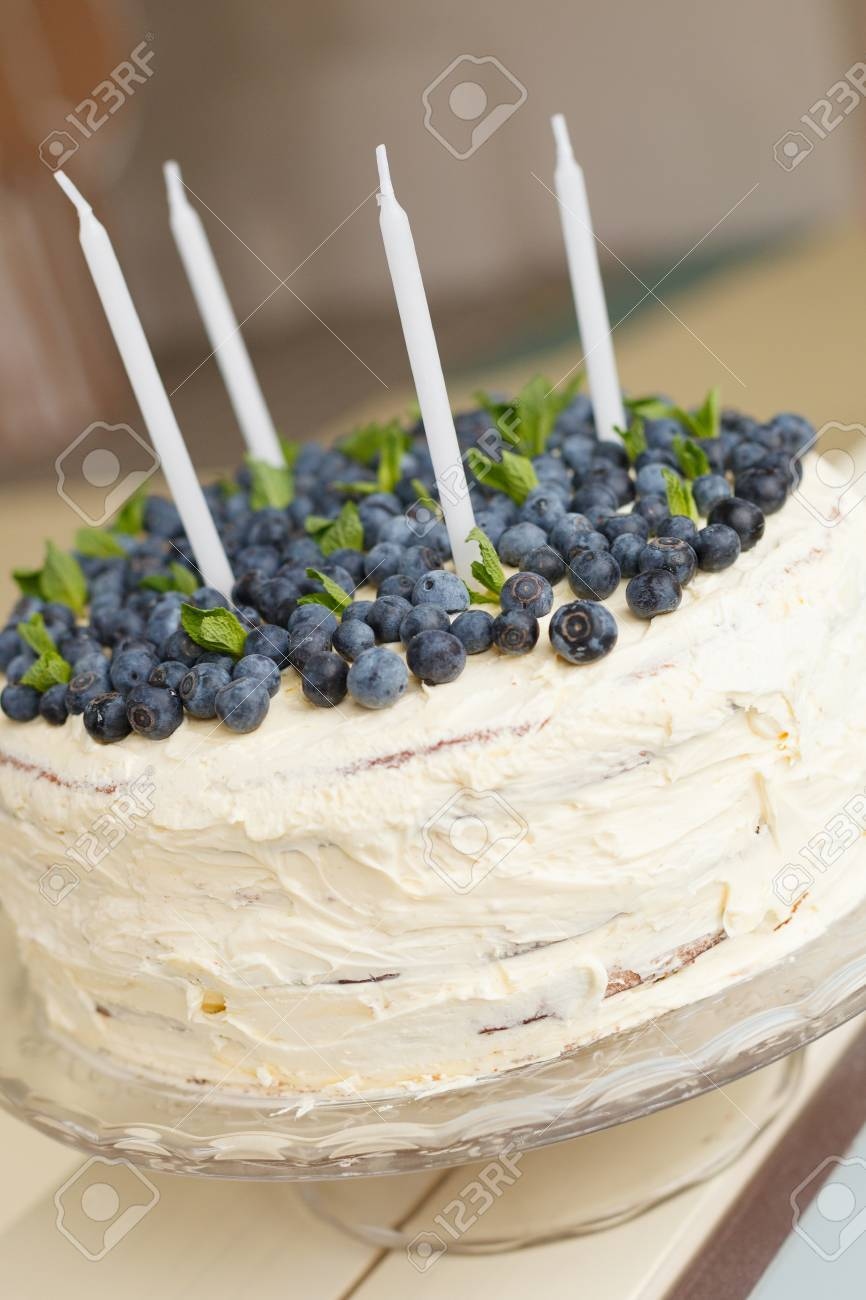 A Big White Birthday Cake With Fresh Organic Blueberries And Mint Candles On The