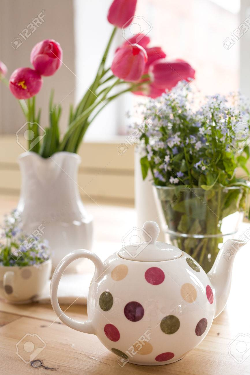 Teapot with dots and vases with beautiful spring flowers on the stock photo teapot with dots and vases with beautiful spring flowers on the wooden table decoration for home interior forget me not and tulips in vases mightylinksfo
