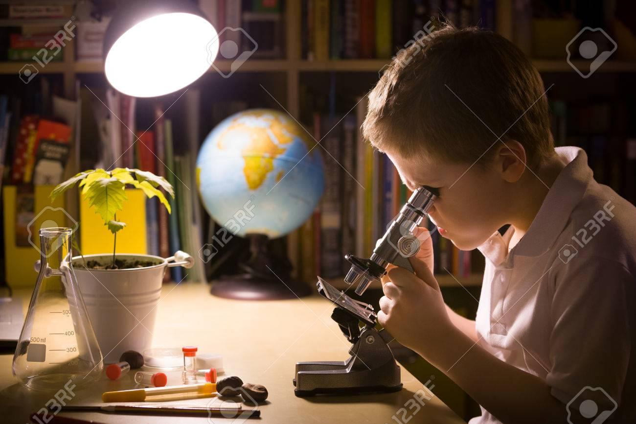Close up porträt der jungen schüler mit mikroskop in seinem zimmer