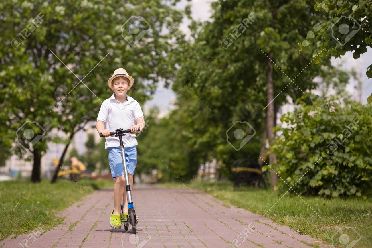 Cute Kid Boy Riding His Scooter And Having Fun In The Park On