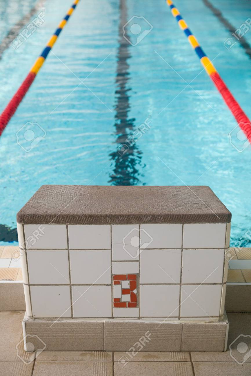 Starting blocks and lanes in a swimming pool. Edge of indoors..