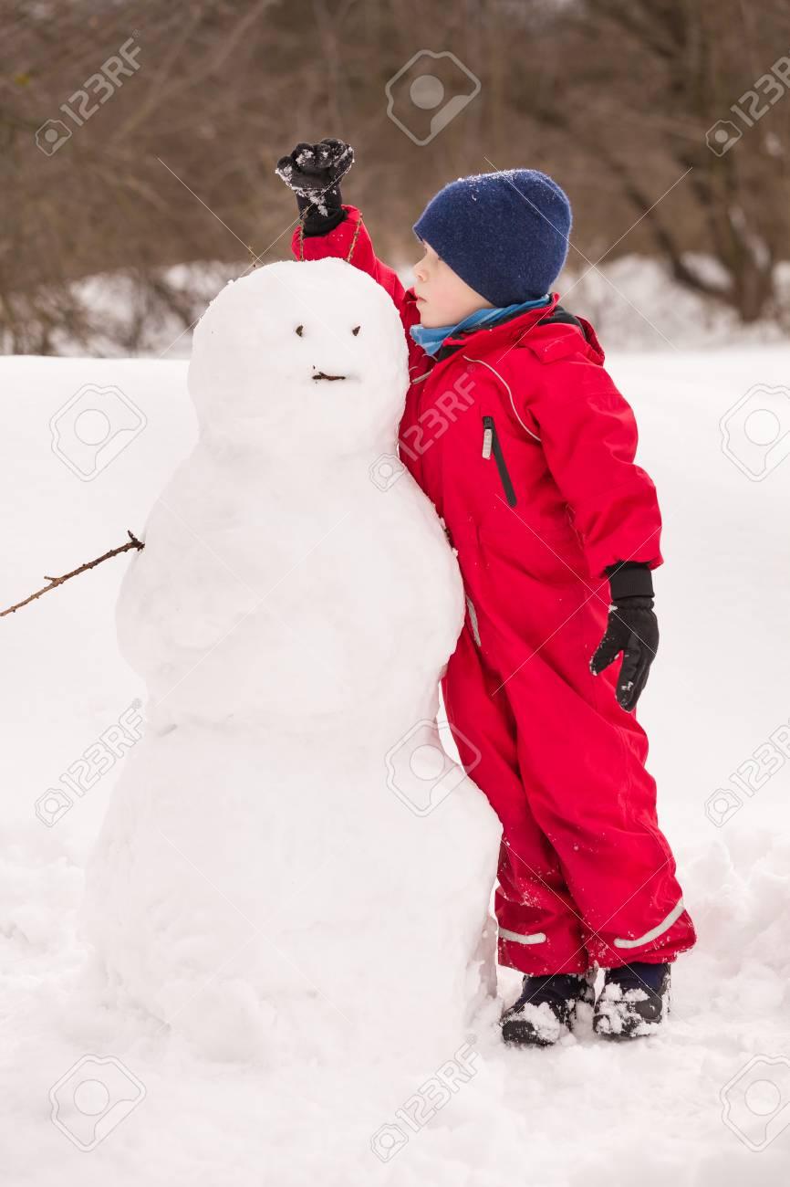 détaillant en ligne 48cff f7926 Portrait mignon enfant garçon vêtements rouges d'hiver faisant grand  bonhomme de neige dans le parc un jour froid ensoleillé. Enfant amuser à ...