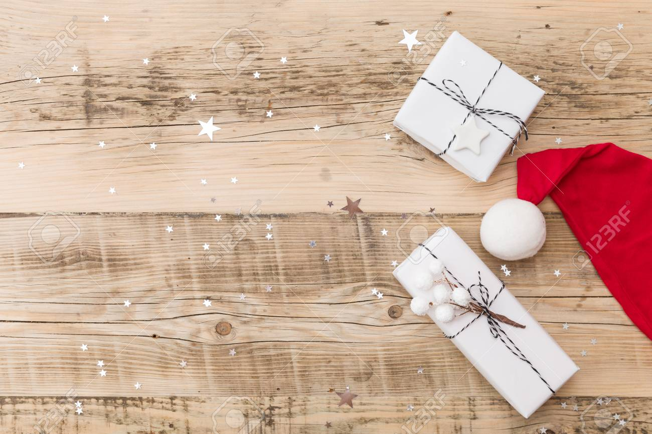 stock photo top view on nice christmas gifts wrapped in white gift paper christmas tree decorations in santas hat on wooden background with sparkling - Nice Christmas Gifts