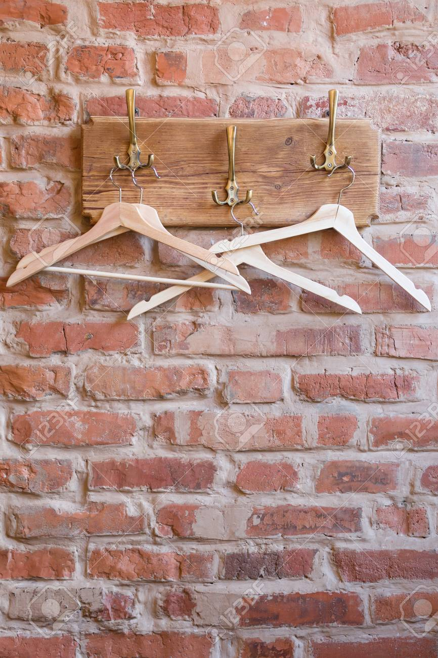 Wooden hangers on the old bricks wall background  Clothes hangers