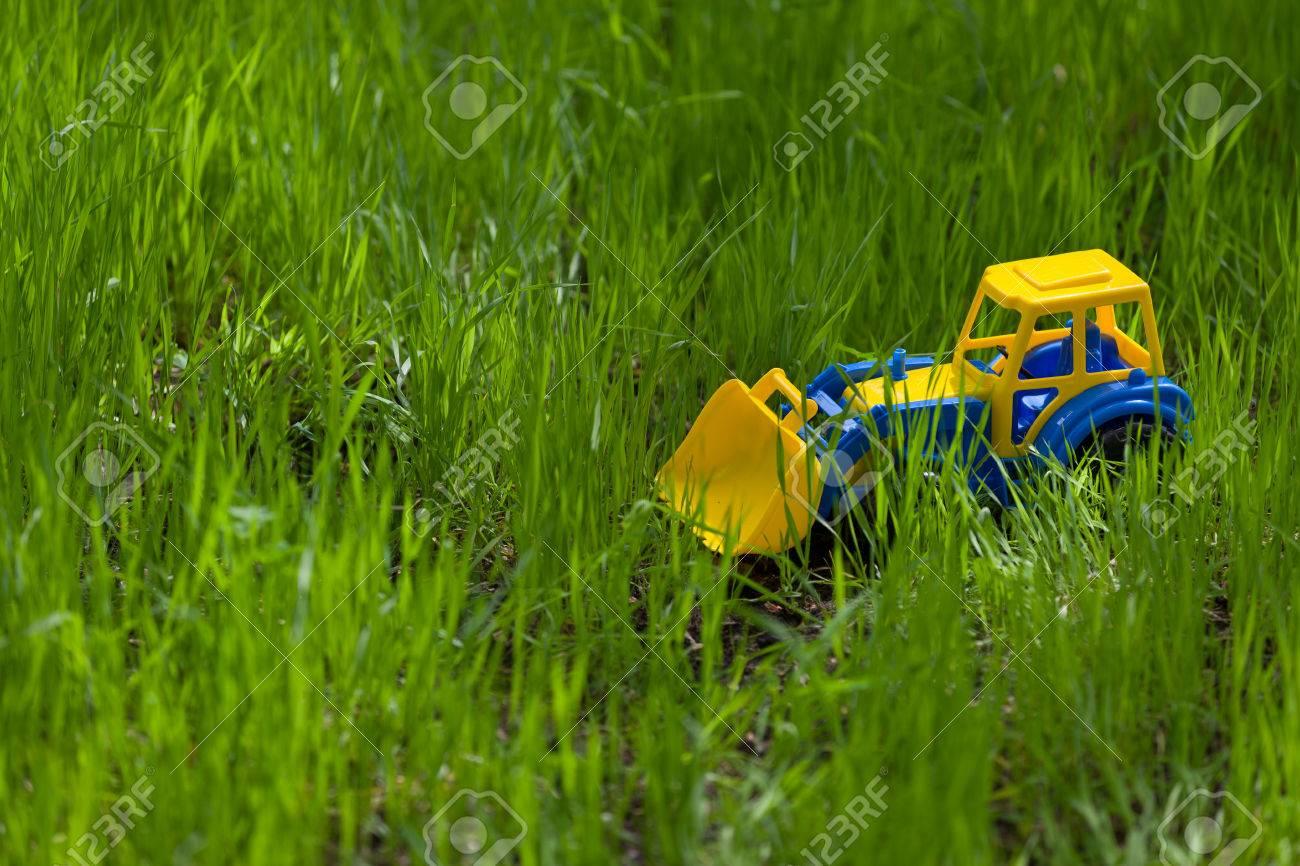 spielzeug bunte traktor im gras. kinderspielzeug im garten. draußen