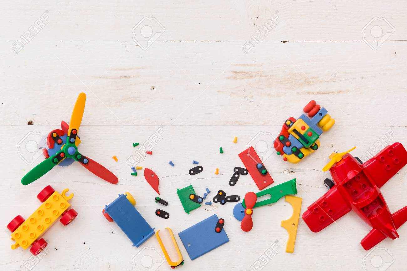 Top View On Colorful Toy Bricks On A White Wooden Background