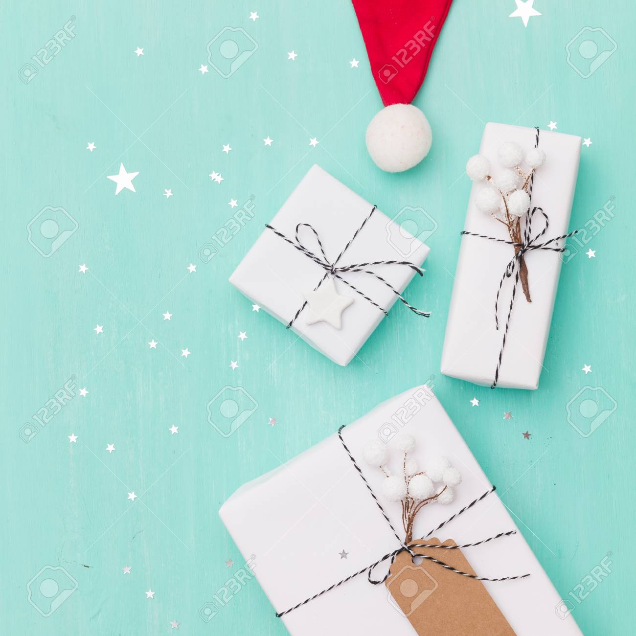 banque dimages closeup of nice christmas gifts wrapped in white paper christmas tree decorations santas hat on wooden background with sparkling stars - Nice Christmas Gifts