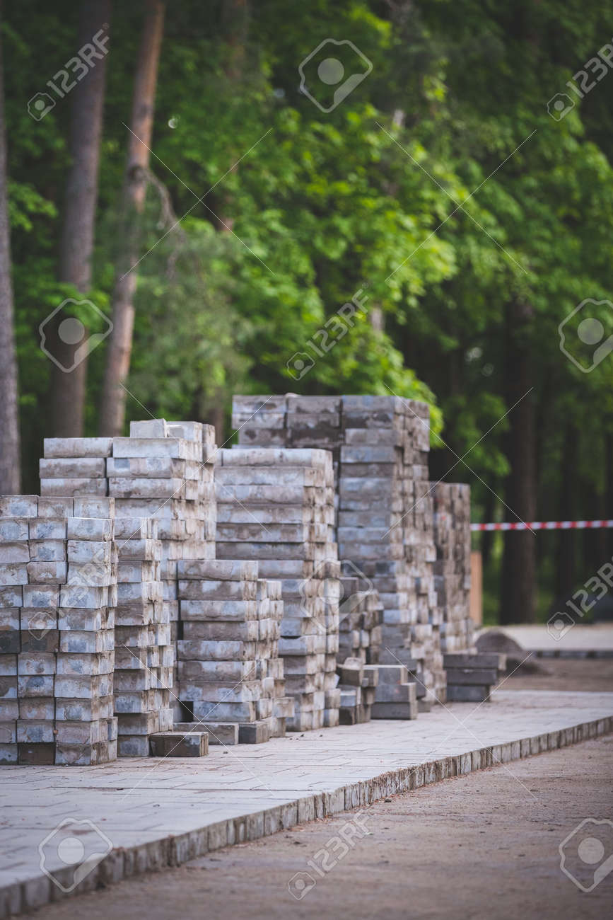 Laying and repairing paving slabs at a construction site on a walkway, against a background of stacked blocks of tiles. Laying of paving slabs in the pedestrian zone, sand filling. - 167371930