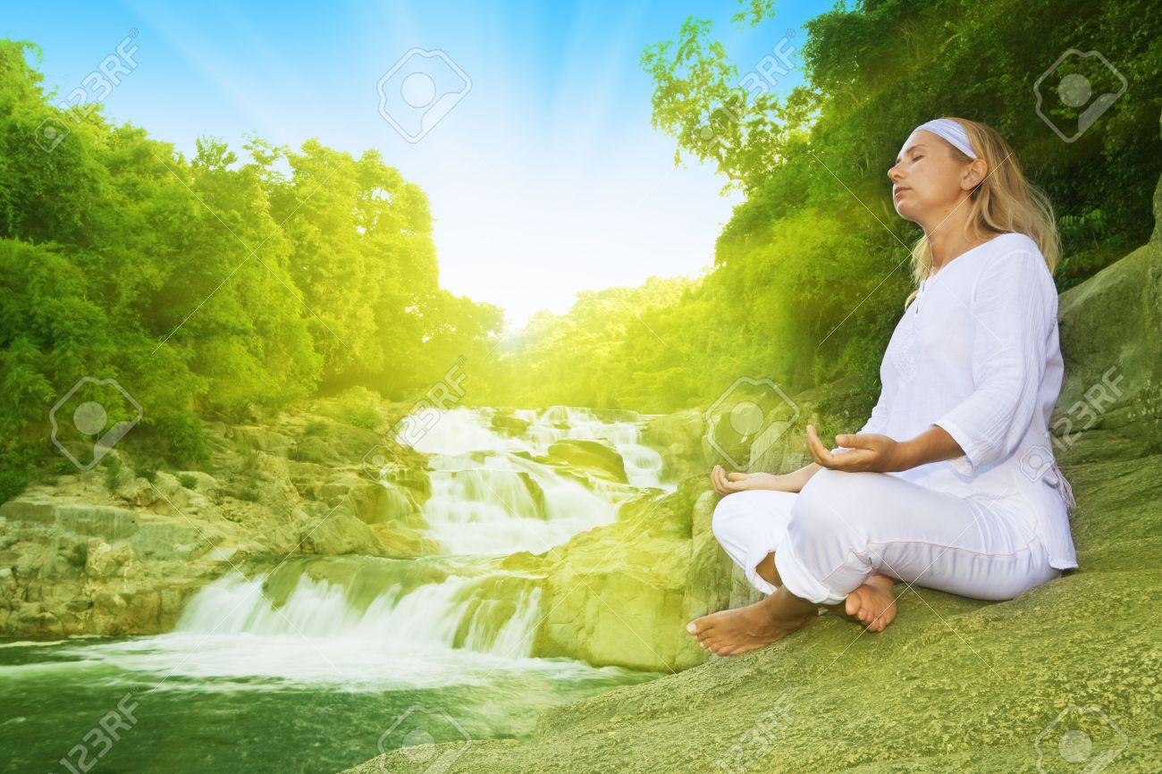 Young woman meditating at sunrise time near waterfall Stock Photo - 3566158