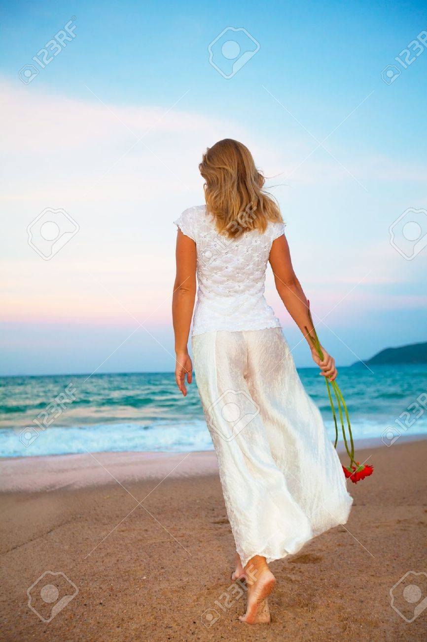 Woman walking on a beach royalty - Young Fashion Woman Walking With Flowers On The Beach Stock Photo 4330726