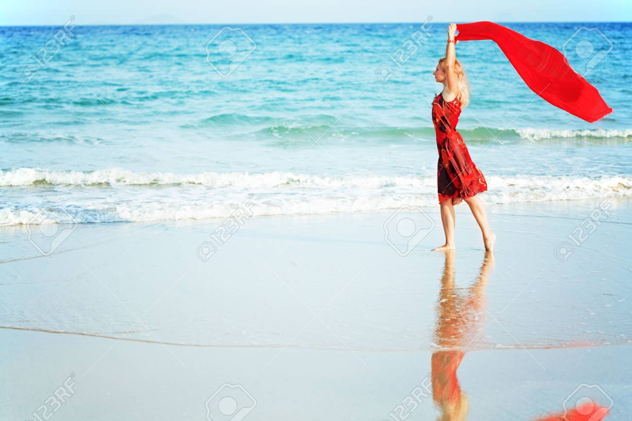 Beautiful woman walking near the ocean with red sarong Stock Photo - 5069756