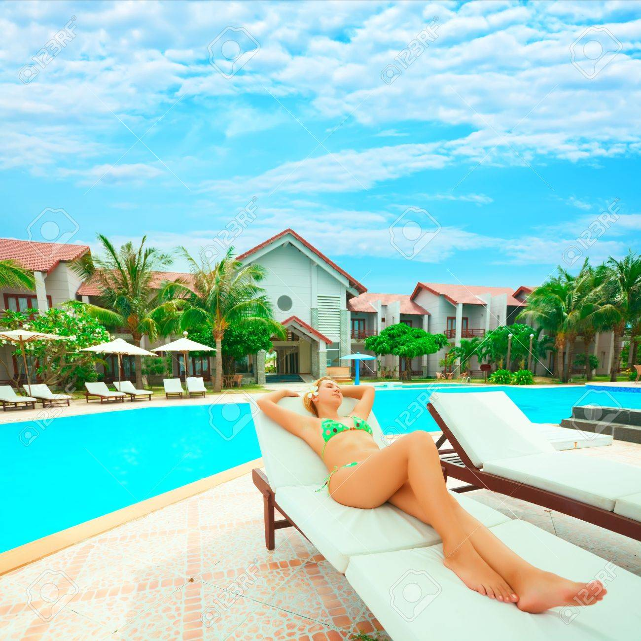 Stock Photo   Young Woman Sunbathing On The Chair Near The Swimming Pool