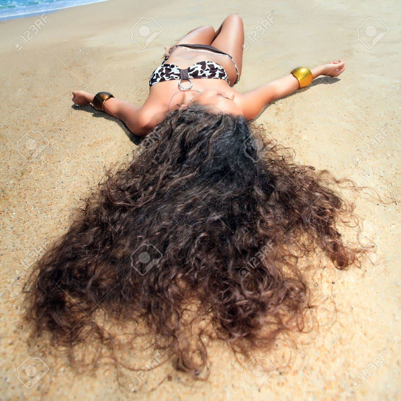 Young beautiful woman is sunbathing on the sand Stock Photo - 6881857