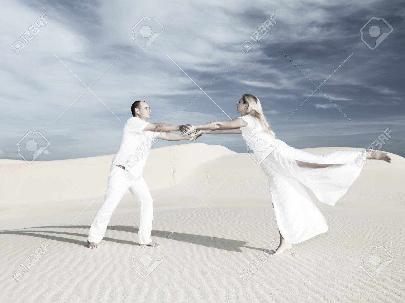 Young couple dancing on desert dune at wedding date Stock Photo - 7539015