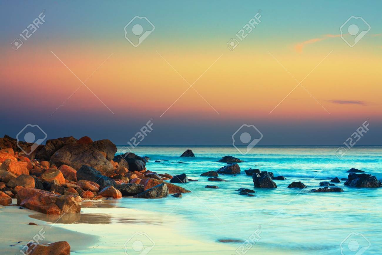 Sunset over the sea. Stone on the foreground Stock Photo - 14305314