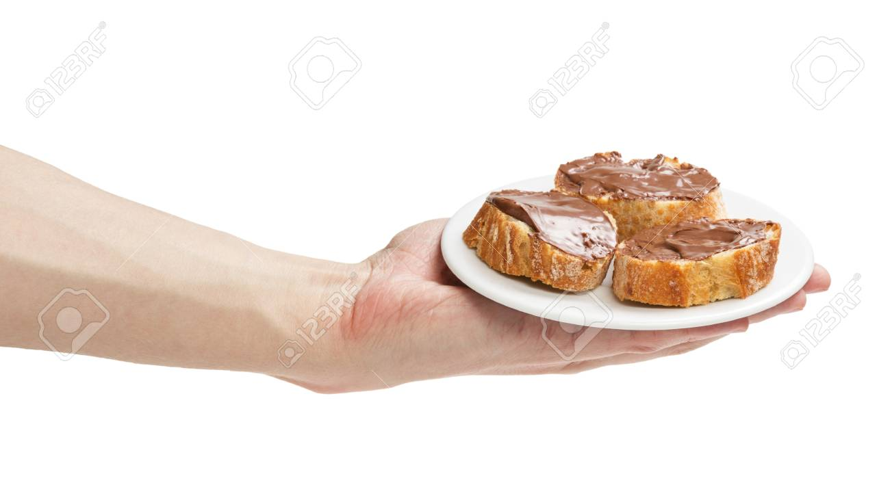 baguette slices spread with nut-choco paste in man hand, isolated on white Stock Photo - 18464191