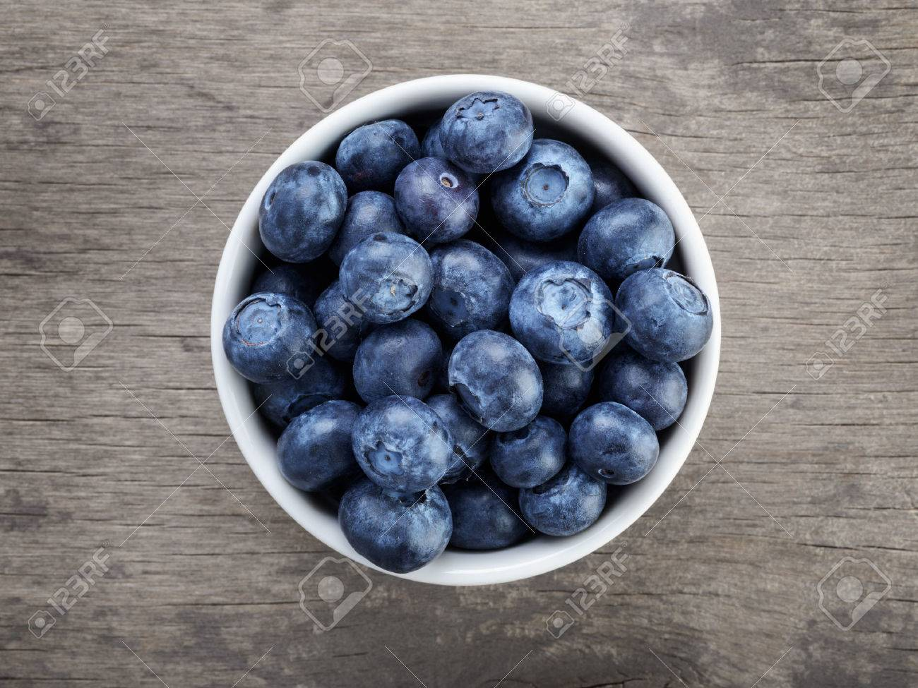 fresh blueberries in white bowl on wood table, rustic style Stock Photo - 25290542