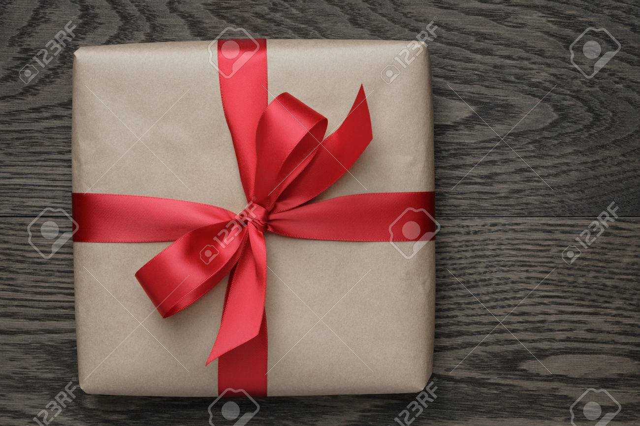 brown gift box with red bow on wood table, top view - 33870893
