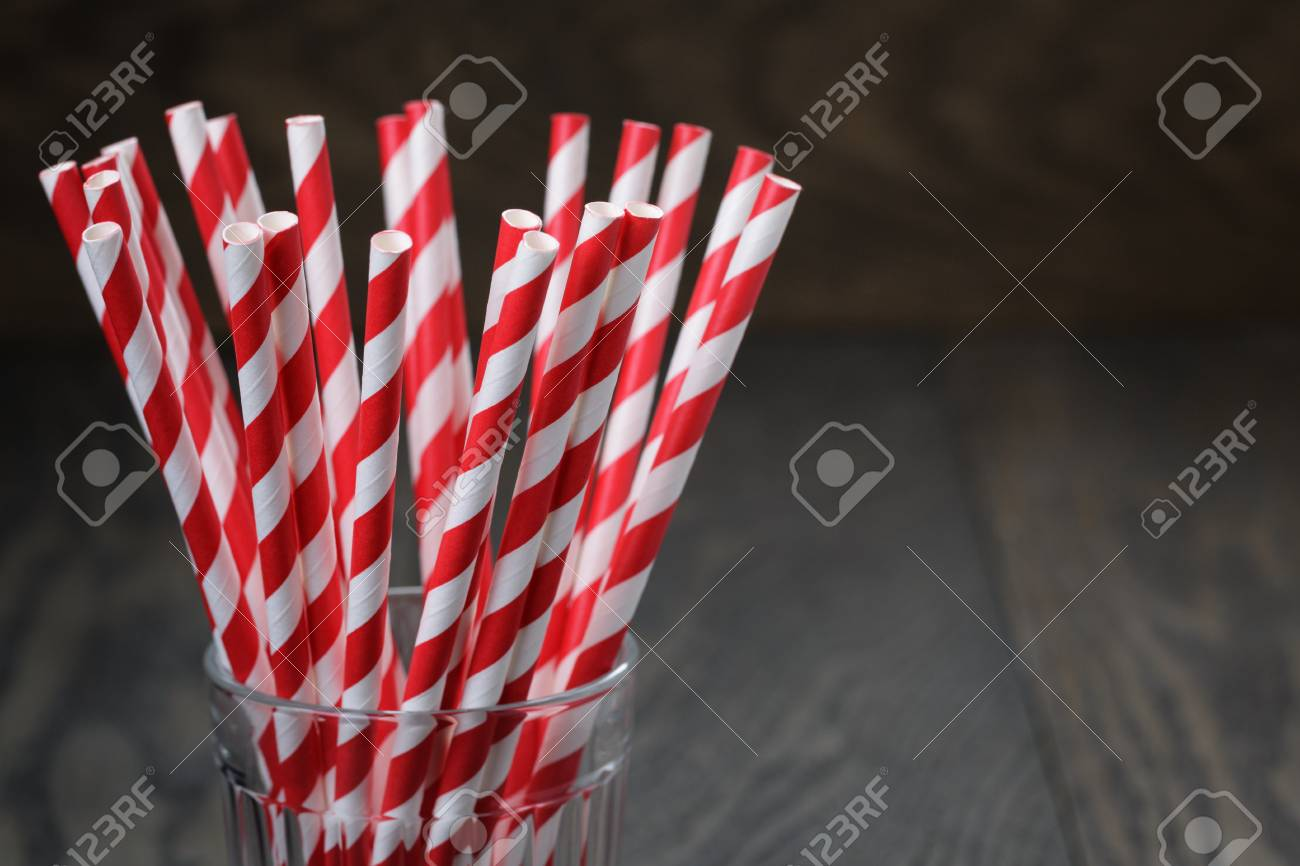 vintage paper straws in glass on wood table, rustic style - 34269858