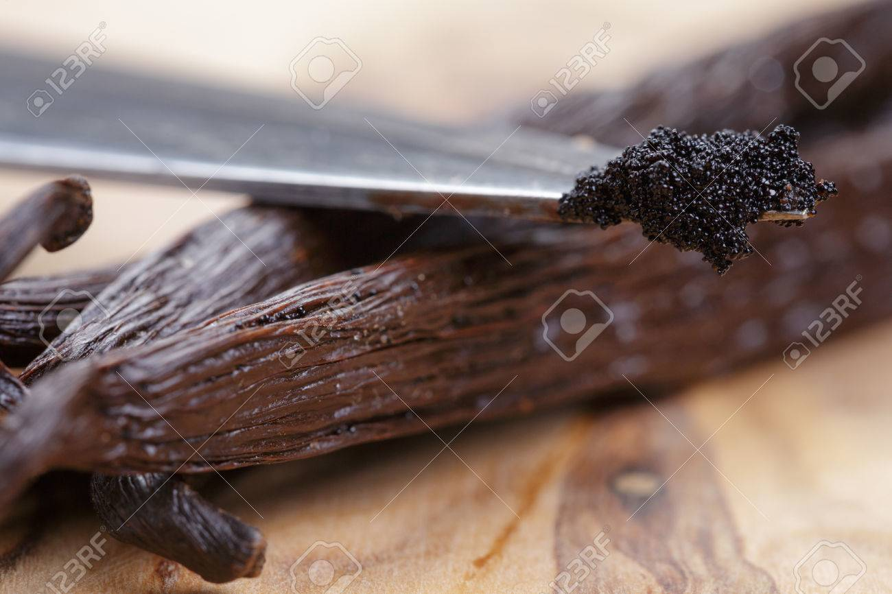 vanilla pod on olive board with beans on knife, close up photo - 34697875