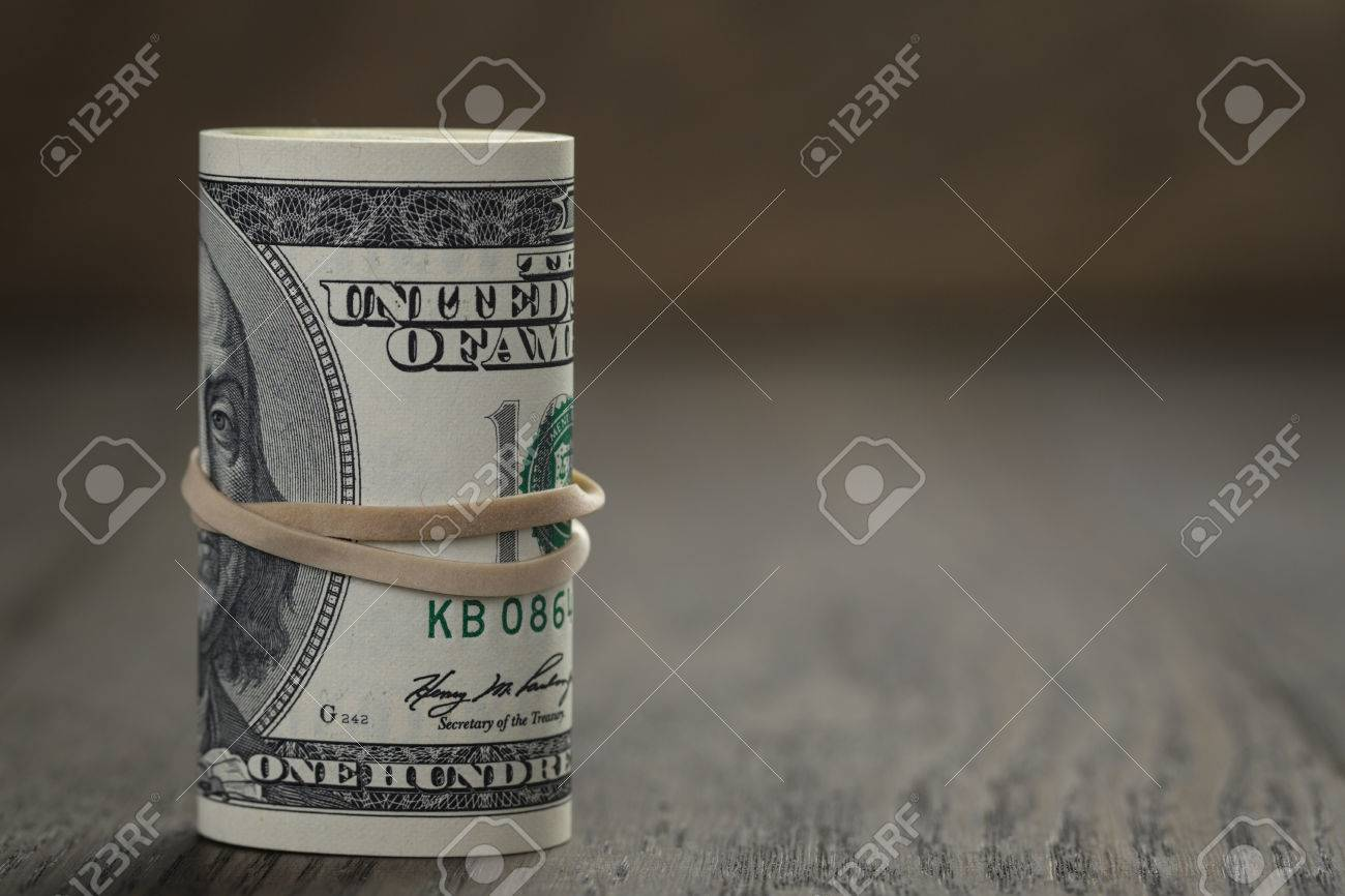 roll of old style hundred dollar bills stand on wooden table - 37907506