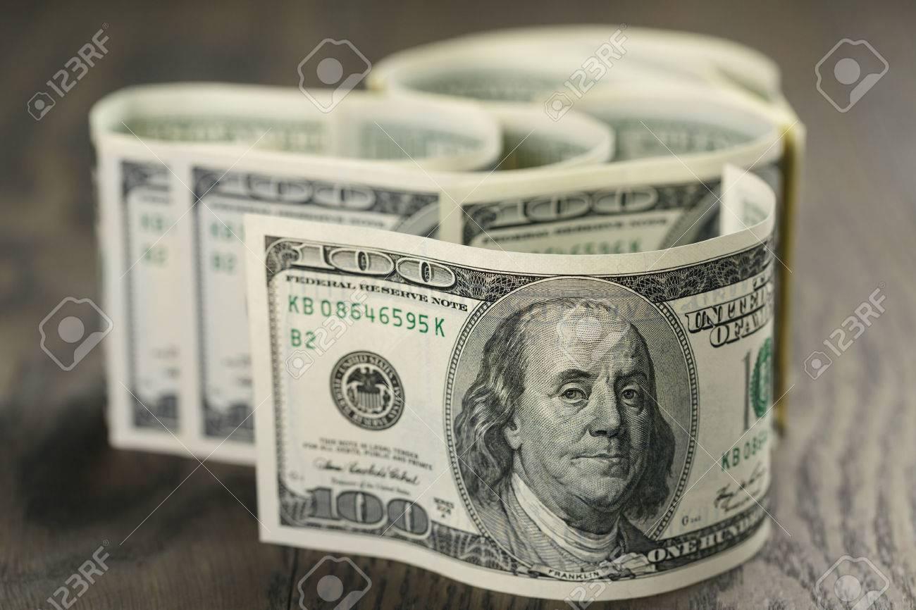 hundred dollar bills on wood table - 38335345