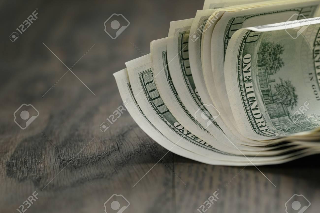 hundred dollar bills on wood table - 38335348