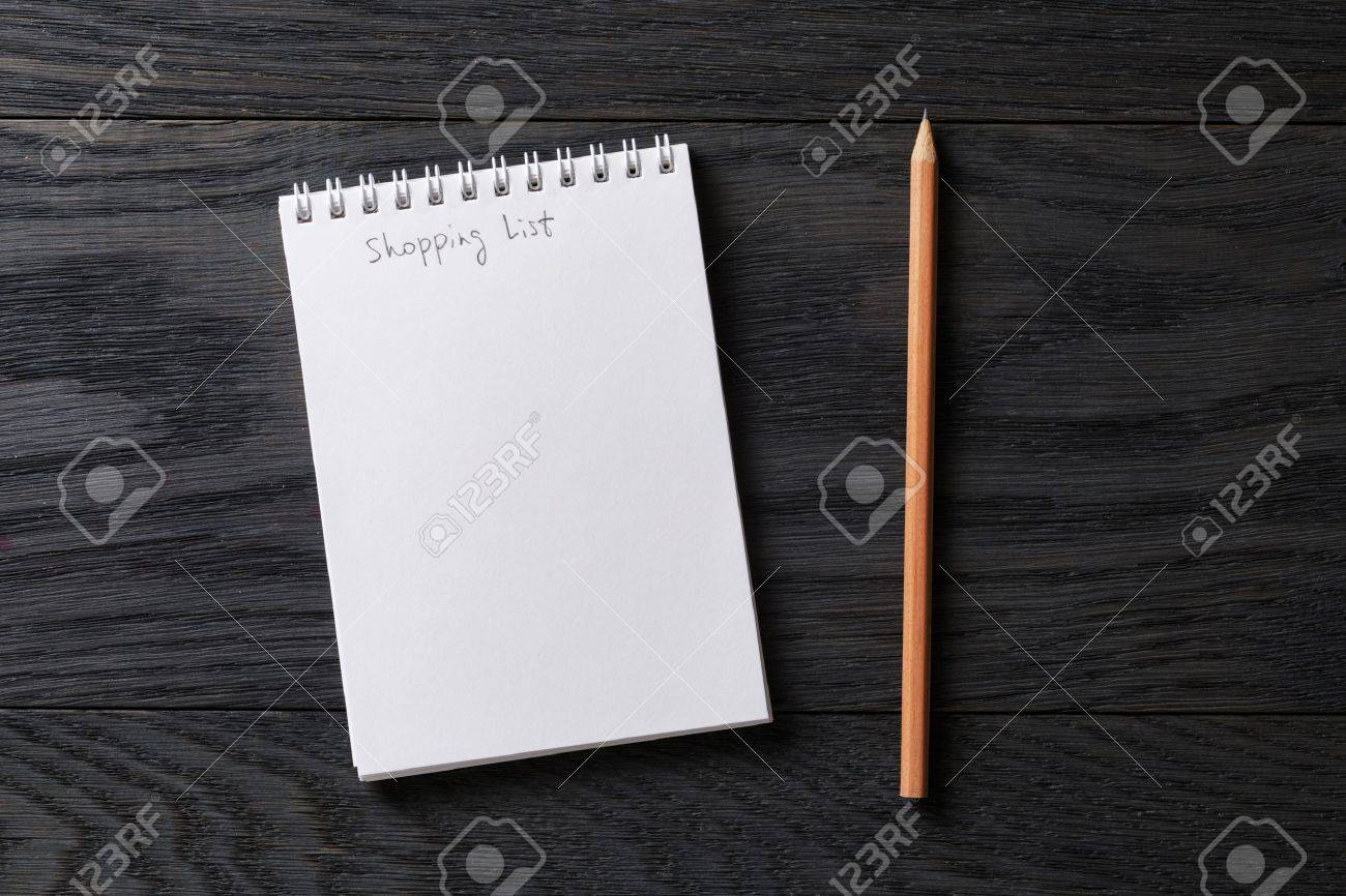 shopping list phrase in notepad on gray wood table, top view - 51084390