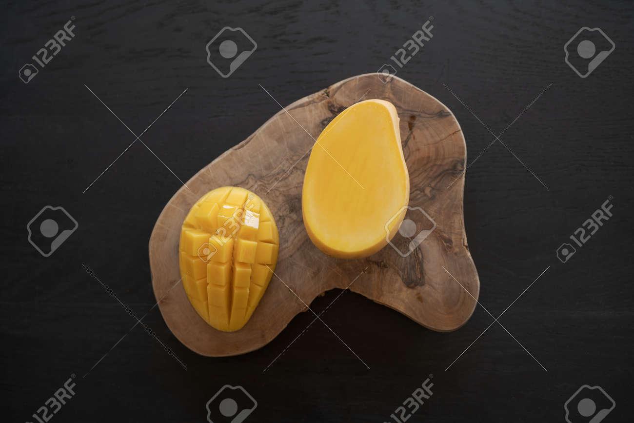 Cut in halves thai yellow mango on olive wood board - 173681395