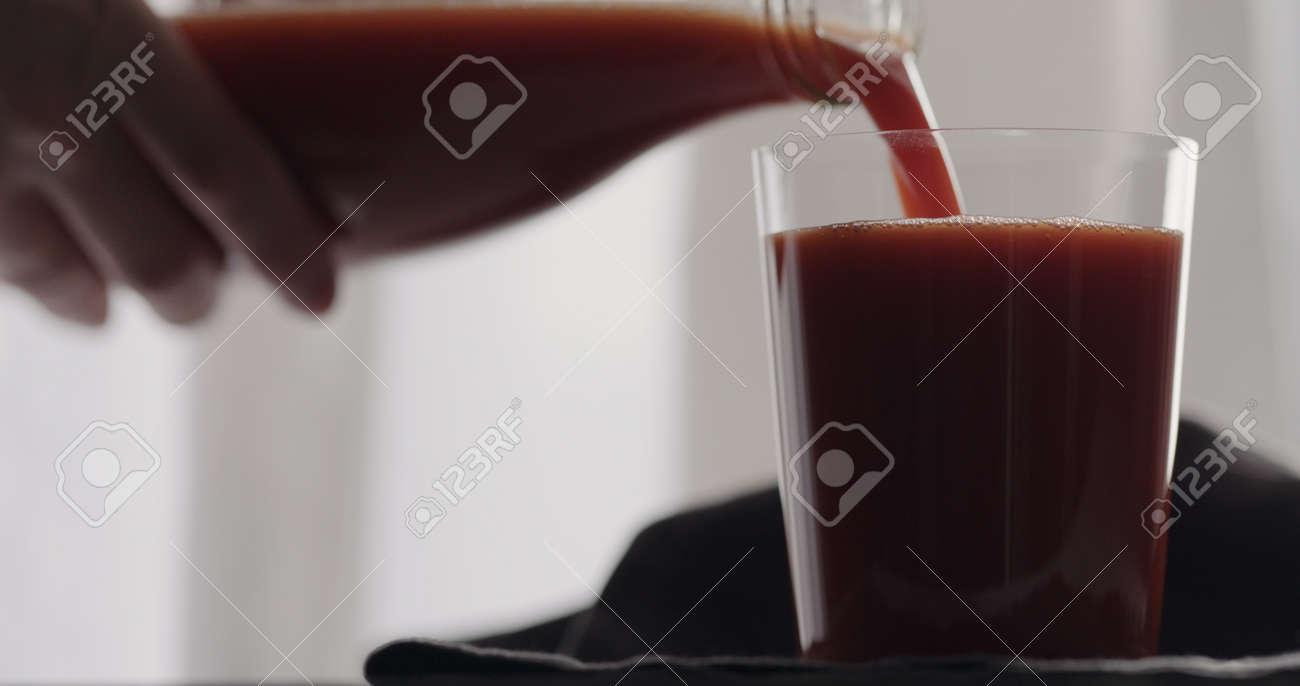 man pour tomato juice into tumbler glass - 174261797